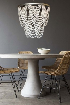 lifestyle image of Contemporary Round Table with Blonde Rattan Dining Chair and White Wooden Beaded Waterfall Chandelier on pale flooring and grey wall background