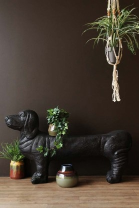 lifestyle image of Cumberland The Sausage Dog Bench with plants on and around with dark brown wall background