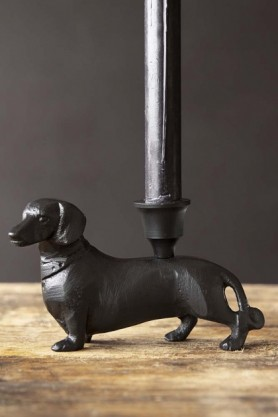Lifestyle image of the Dachshund Sausage Dog Candle Holder with tall black candle and on wooden surface with dark wall background