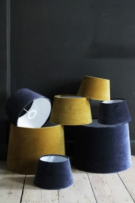 lifestyle image of Dandelion Yellow Sumptuous Velvet Lamp Shade - Small and dark blue velvet shades in pile on wooden floor and dark wall background