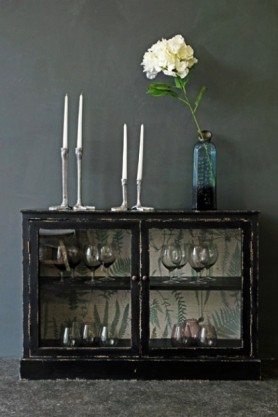 lifestyle image of Distressed Black Display Cabinet With Botanical Lining with glasses inside and candlesticks and blue vase with flower in on top and dark grey wall background