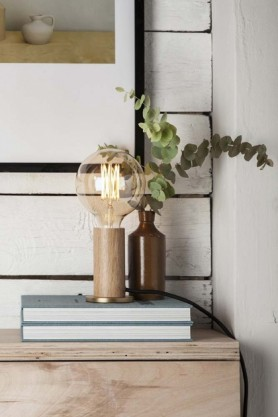 lifestyle image of E27 Dimmable 6W Tinted LED Giant Globe Bulb lit up with brown vase with eucalyptus in on pile of books on chest of drawers and picture frame on wall