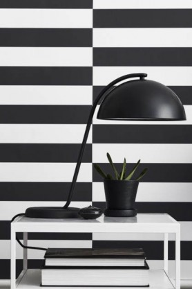 Lifestyle image of Engblad & Co Thick Vertical Stripe Wallpaper - Black & White with white desk, large black table lamp and plant in black pot