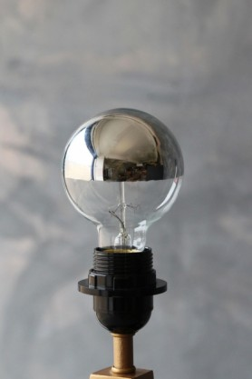 lifestyle image of ES27 40W Small Globe Squirrel Cage Bulb with grey wall background