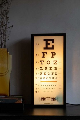 Lifestyle image of the Vintage Eye Test Light Box lit up on a shelf
