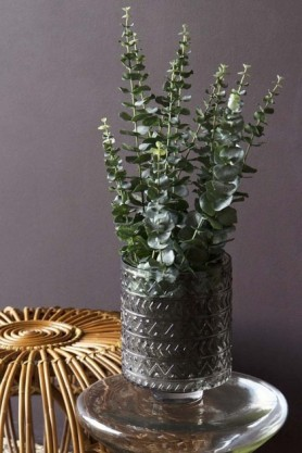 Lifestyle image of the Faux Eucalyptus Plant For A Pot in a grey glass vase and on glass side table with dark wall background