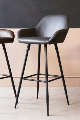 Lifestyle image of Faux Leather Bar Stool With Zig Zag Stitching - Charcoal Grey with second stool in background on pale wooden floor and contrasting wall background