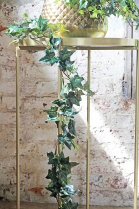 lifestyle image of Faux Trailing Ivy Garland - 185cm on gold tray side table with white distressed brick wall background