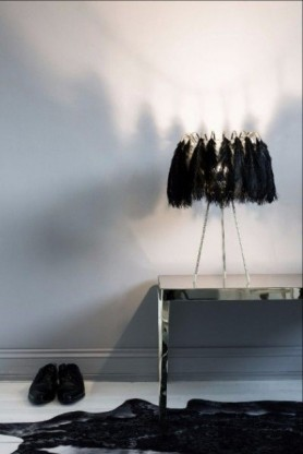 Feather Table Lamps In Black turned on with pale wall background and dark cowhide lifestyle image