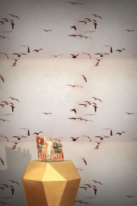 lifestyle image of Feathr Portuguese Seagulls Wallpaper - Dusty Pink with gold side table with family at beach ornament on