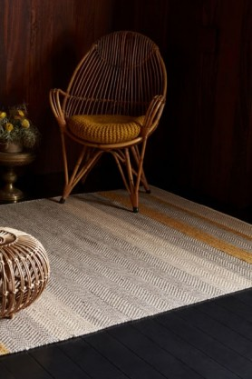 lifestyle image of Fields Stripey Rug - Various Colours & Sizes with rattan armchair and dark lighting