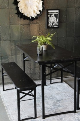 lifestyle image of Foldable Picnic Table With 2 Benches on top of grey rug and with plant in grey pot on top of table and picture frame and feather ornament hung on grey tiled wallpaper background
