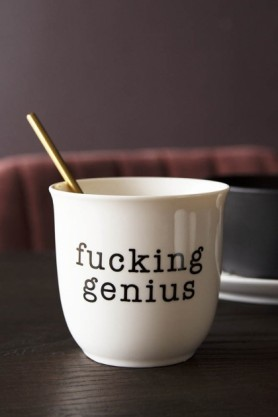 Lifestyle image of the Fucking Genius Bone China Mug with spoon inside on black table with other tableware and red velvet chair and dark wall background