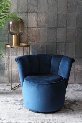 lifestyle image of Gallery Velvet Cocktail Chair - Midnight Blue with gold tray side table and table lamp and plant on grey patterned rug and grey tiled wallpaper background