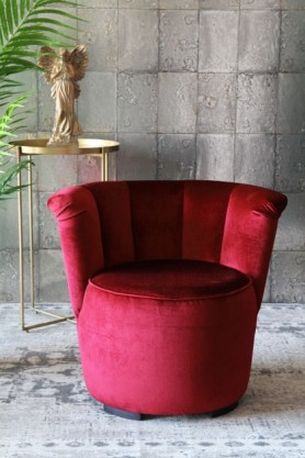 lifestyle image of Gallery Velvet Cocktail Chair - Pinot Noir Red with gold side table and Gold finish angel ornament and plant on grey patterned rug and grey tiled wallpaper background