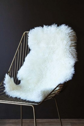 lifestyle image of Genuine New Zealand Long Wool Curly Sheepskin - Off White on midas chair with dark wall background