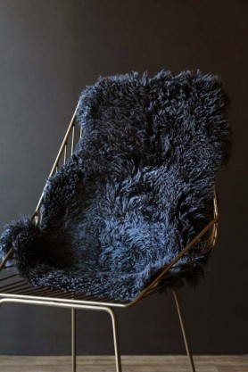 lifestyle image of Genuine New Zealand Long Wool Curly Sheepskin - Steel on midas chair with dark wall background