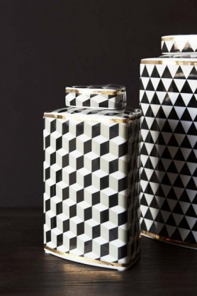 Lifestyle image of the short Geometric Monochrome Storage Jar with Gold Detail  next to Geometric Monochrome Storage Jar with Gold Detail - Tall on black side table and dark wall background