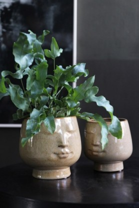 lifestyle image of Glazed Peaceful Faces Flower Pot with plant in on black table and dark painting on grey wall background