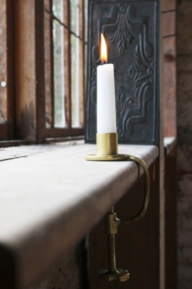 lifestyle image of Gold Clamp Candle Holder clamped on windowsill and candle lit