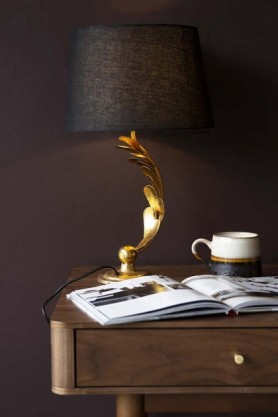Lifestyle image of the Gold Curved Leafy Stem Table Lamp switched on on wooden side table with book open and mug with dark wall background
