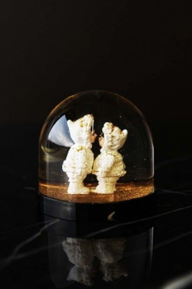 lifestyle image of Gold Eskimo Kiss Snow Globe on black table with black wall background