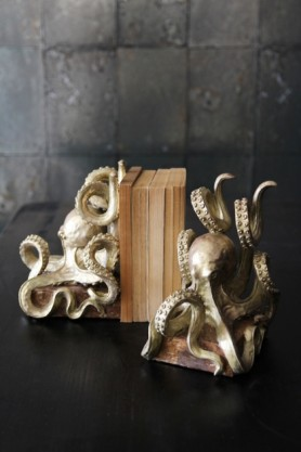 lifestyle image of Gold Octopus Bookends with books in between on black table with Cole & Son Mariinsky - Antique Mirror Wallpaper background