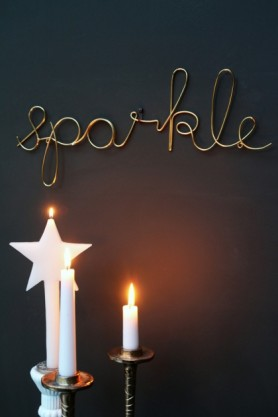 lifestyle image of Gold Sparkle Sign on grey wall above candlesticks and lit candles