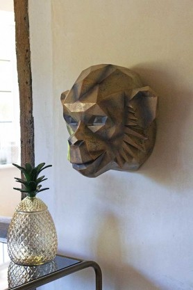 Angled lifestyle image of the Gold Art Deco Monkey Head Wall Decoration