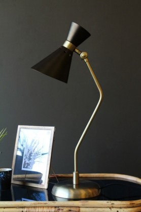 lifestyle image of Grace Black & Gold Table Lamp on black table with picture frame and grey wall background