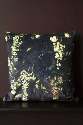 Lifestyle image of the Grape Vine Velvet Cushion on black bench on dark wall background