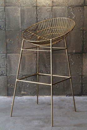 lifestyle image of Hampstead Gold Bar Stool with grey tiled wallpaper background and grey flooring