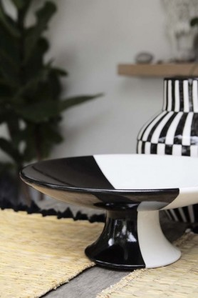 lifestyle image of Handmade Moroccan Black & White Bowl On Stand - 30cm on table with Natural Wicker Placemat With Black Tassels and black and white vase