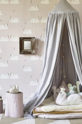 lifestyle image of Hibou Home Swans Children's Wallpaper - 2 Colours Available with grey circular curtain over blankets and pillows with pink pouffe and mirror on wall