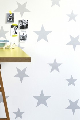 lifestyle image of Hibou Home Wish Upon A Star Children's Wallpaper - Silver/White with wood and gold table and black and white photographs taped onto wall