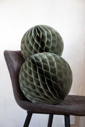 Image of the Set Of 2 Honeycomb Ball Decorations In Moss Green on a chair