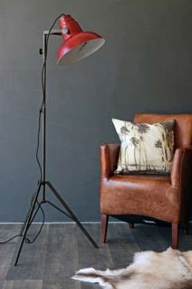 lifestyle image of Industrial Film Floor Lamp With Red Shade with leather armchair with palm tree cushion on and sheepskin on wooden floor and dark wall background