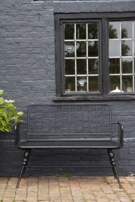 Lifestyle image of the Industrial-Style Black Metal Two-Seater Bench in an outdoor setting on black brick wall with plant and window