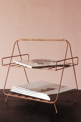 lifestyle image of Iron and Bamboo Magazine Rack with magazines inside on brown wooden table and pink wall background