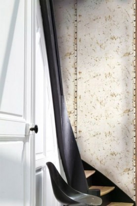 lifestyle image of Koziel Rusted Metal Plate Wallpaper with white door and window with dark curtain
