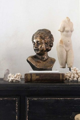 Lifestyle image of the Distressed Antique Gold Gisele Lady Bust sat on a sideboard amongst other display items