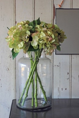 Large Glass Jar Vase with flowers inside on black table and white wood wall background lifestyle image