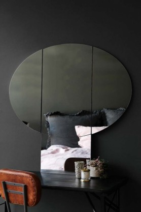lifestyle image of Large Side-View Mushroom Mirror with bed in reflection and brown leather chair