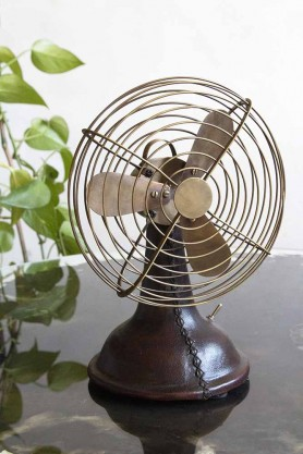 Lifestyle image of the Mini Brass Desk Fan With Leather Base on a light background