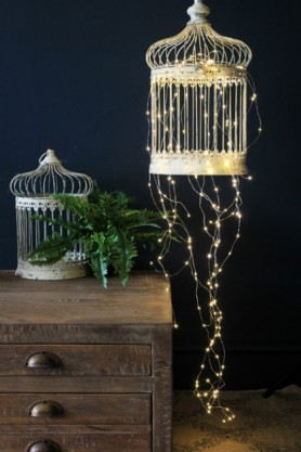 LED Bud Light Spray - Suitable For Indoor And Outdoor Use - Lifestyle Image with wooden drawers dark background and plant in cage