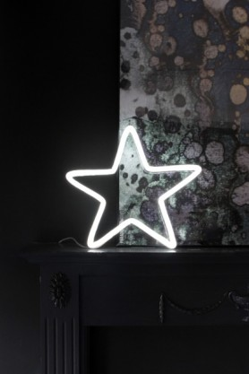 lifestyle image of LED Neon Light - Star - White lit up on black fireplace with oil slick effect wall background