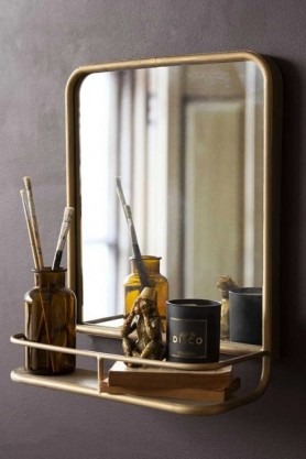 Lifestyle image of the Light Gold Almost Square Bathroom Mirror With Shelf with decor in shelf on dark wall background