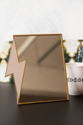 Lifestyle image of the Lightning Bolt Desk Mirror on black desk and pale wall background