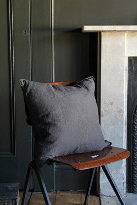 lifestyle image of Lisbon Soft Linen Cushion - Slate Grey on wooden chair with white fireplace and grey wall background