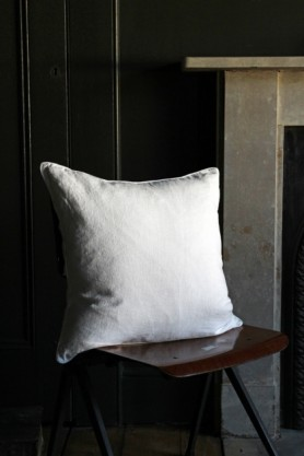 lifestyle image of Lisbon Soft Linen Cushion - White on wooden chair with white fireplace and grey wall background